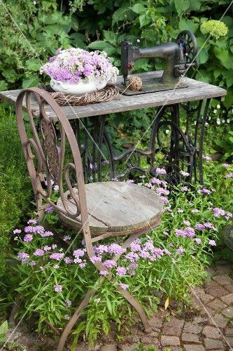 Vintage stuhl vor alter n hmaschine mit blumenschale und weidenkranz in bl hendem garten - Shabby gartendeko ...