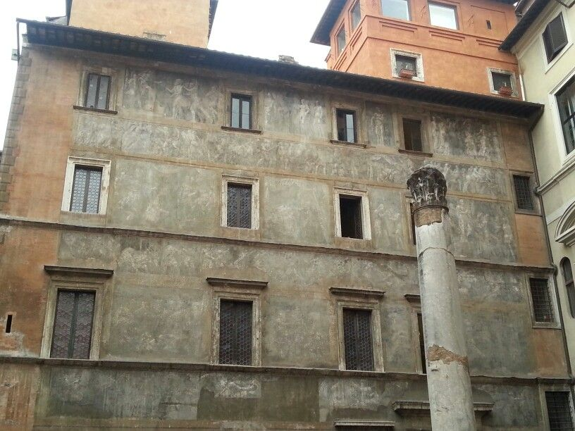 Ancient Roman column with monochrome Renaissance frescoes backdrop. Downtown Rome