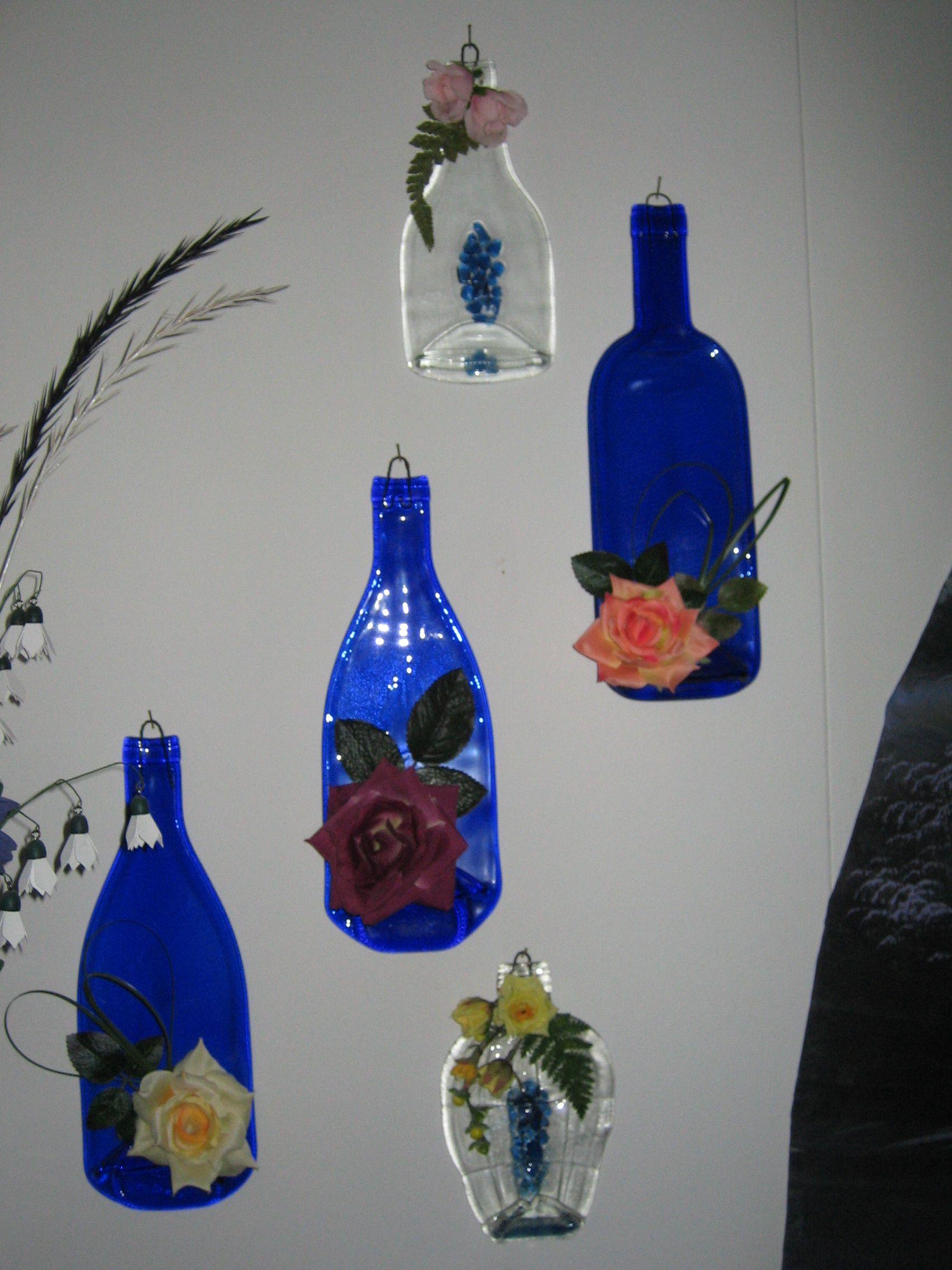 Lasipulloja sulatettu posliininpolttouunissa ja koristeltu keinokukkasin