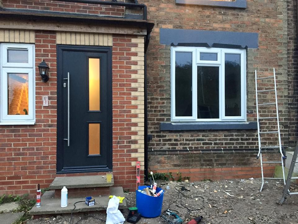 Grey composite front door with long windows and long bar handle ...