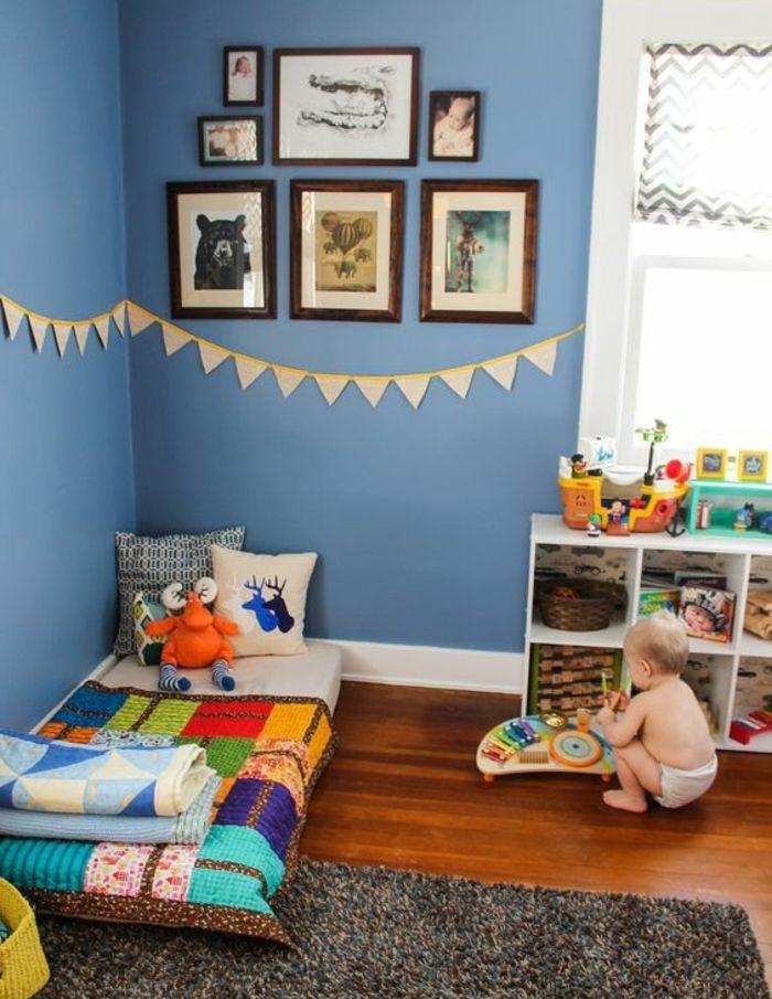 ide dco chambre enfant mur couleur bleue deco murale lit bb montessori au sol tapis gris meuble de rangement bas couverture de lit multicolore