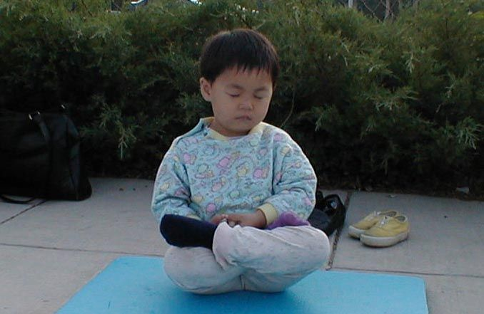 Young Practitioner in Meditation  Young Falun Dafa diciple sits in meditation outside a Metro entrance during morning practice, 2001.