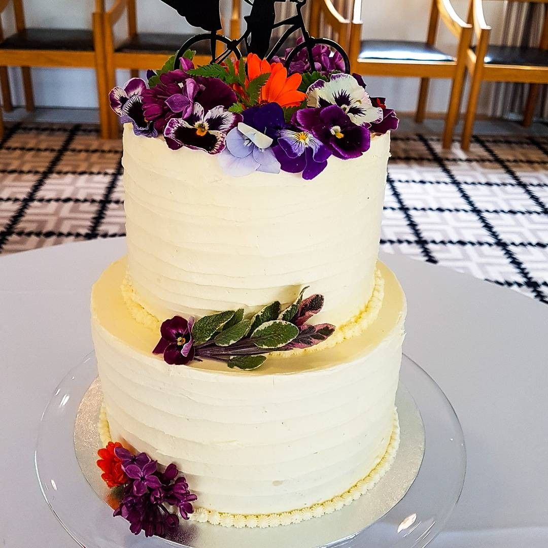 A colourful 2 tier wedding cake with shades of purple edible flowers ...