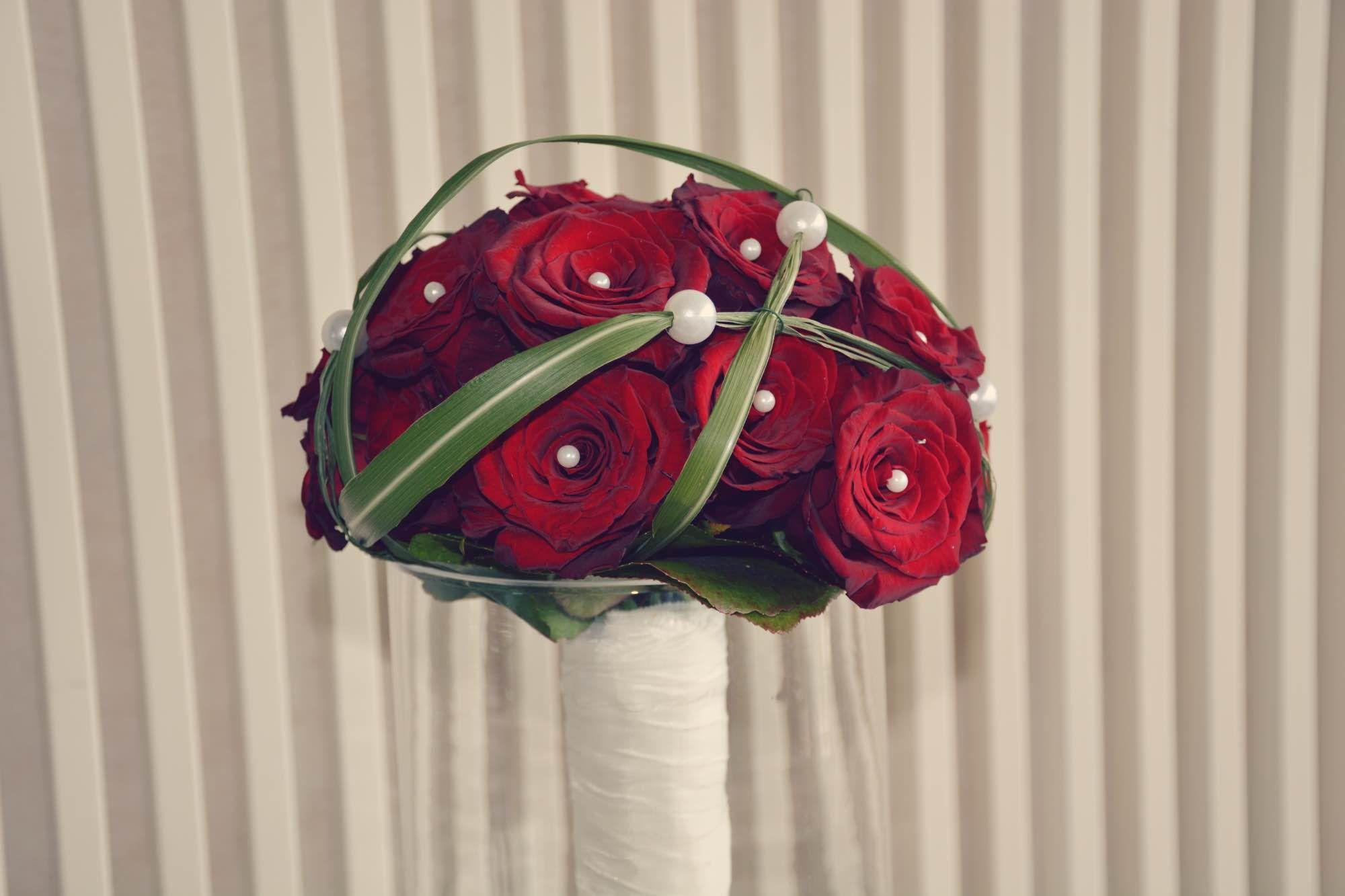 Rote Rosen verziert mit Perlen als Brautstrau