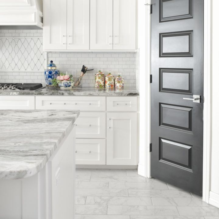 Homeowners Guide to Black Interior Doors - Monica Wants It #whitemarbleflooring White kitchen, walls and trim with marble floors and countertops and black interior pantry kitchen door. Tips, hacks on how to clean dark doors to remove dust, fingerprints and pet hair. #decoratingkitchen #kitchendesign #kitchenideas #kitchendecor #kitchenremodel #kitchens #whitemarbleflooring