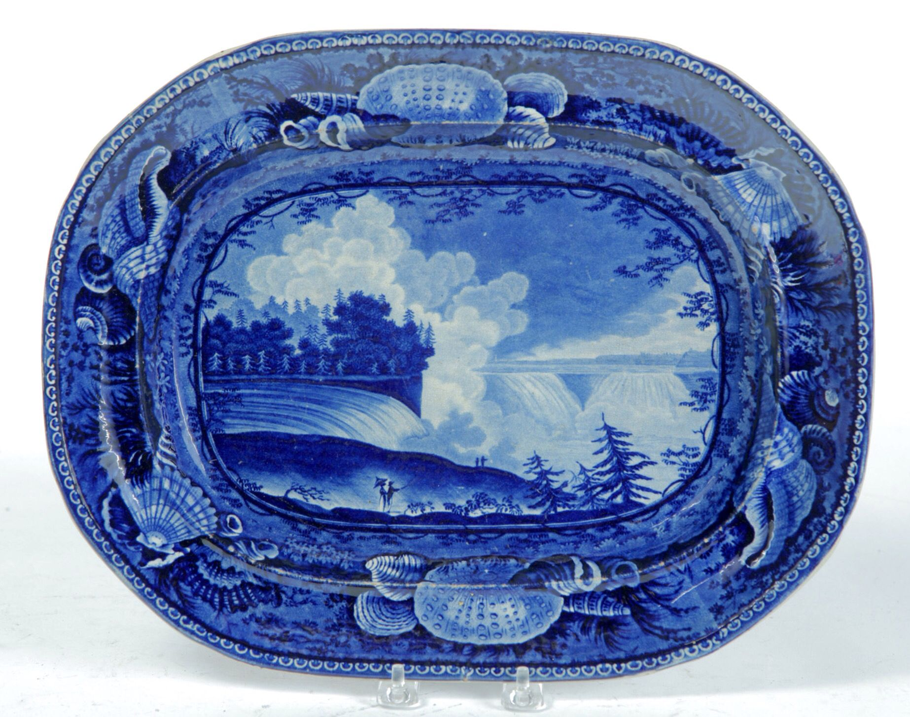 """Garth's Sale 1129 Lot 461 Mar 13 2015.  HISTORICAL BLUE STAFFORDSHIRE PLATTER.  England, 1st half-19th century. Niagara from the American Side impressed Wood & Sons. Shell border. Stains. 11.5"""" x 14.75"""".  Estimate $ 300-600. Sold for $780.   Wear, knife scratches, on the front side, the wear is worst on the high spots (interior rim), and on glaze line that follows the ridge on the near side of the falls and on the left falls as well. The back side displays crazing and staining, and has a 5""""…"""