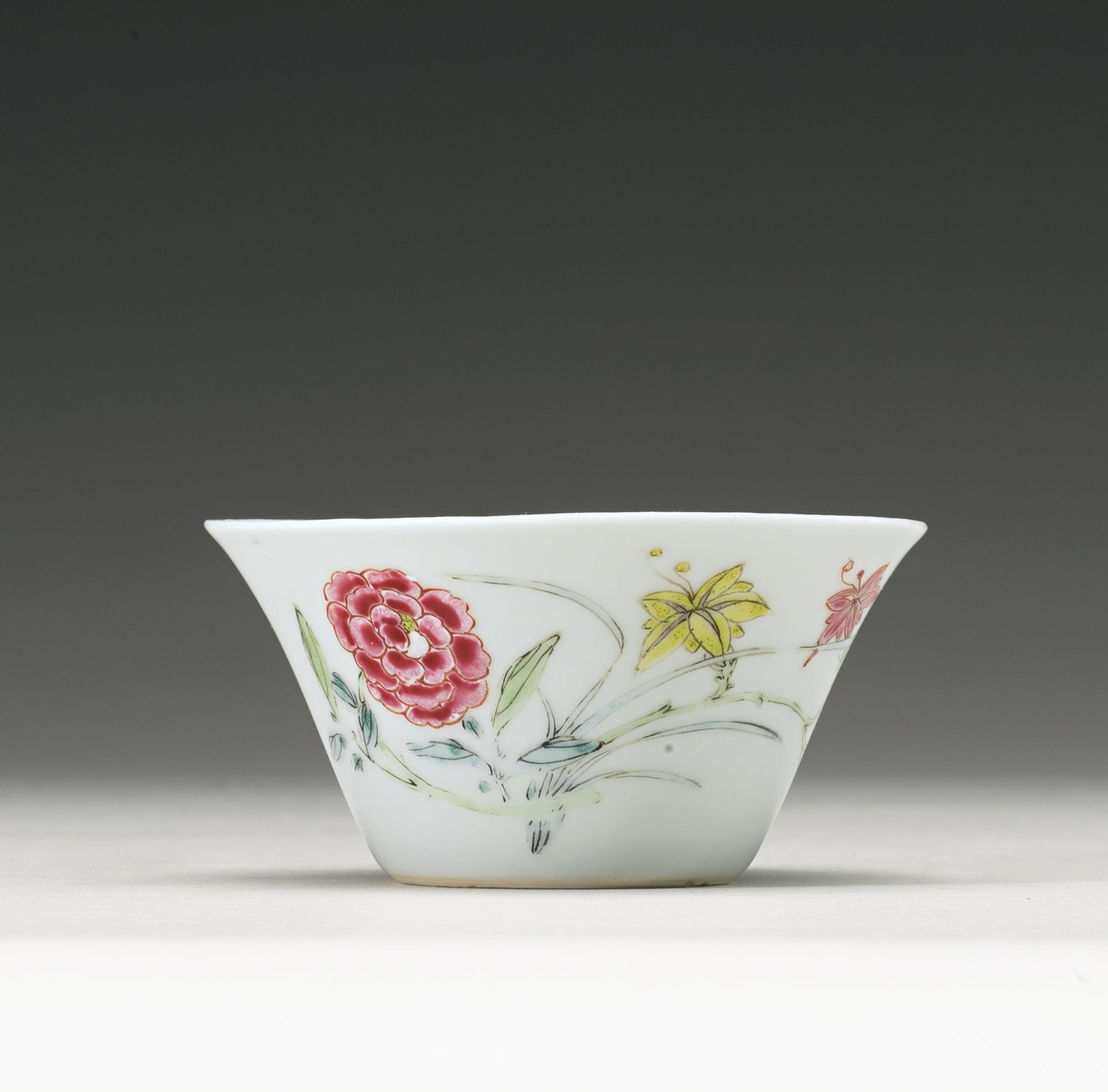 A FAMILLE-ROSE ENAMELED CUPYONGZHENG MARK AND PERIOD thinly potted with a flared rim, the sides delicately painted in pastel enamels with a peony spray, day lilies and a detached chrysanthemum, together with a butterfly, the interior with one floral spray, six-character mark in underglaze blue within a double circle on the indented base Diameter 3 3/8 in
