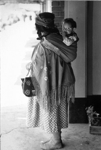Colville mother carrying child in sling on back, Washington, 1939. Northwest Museum of Arts and Culture, American Indians of the Pacific Northwest Collection