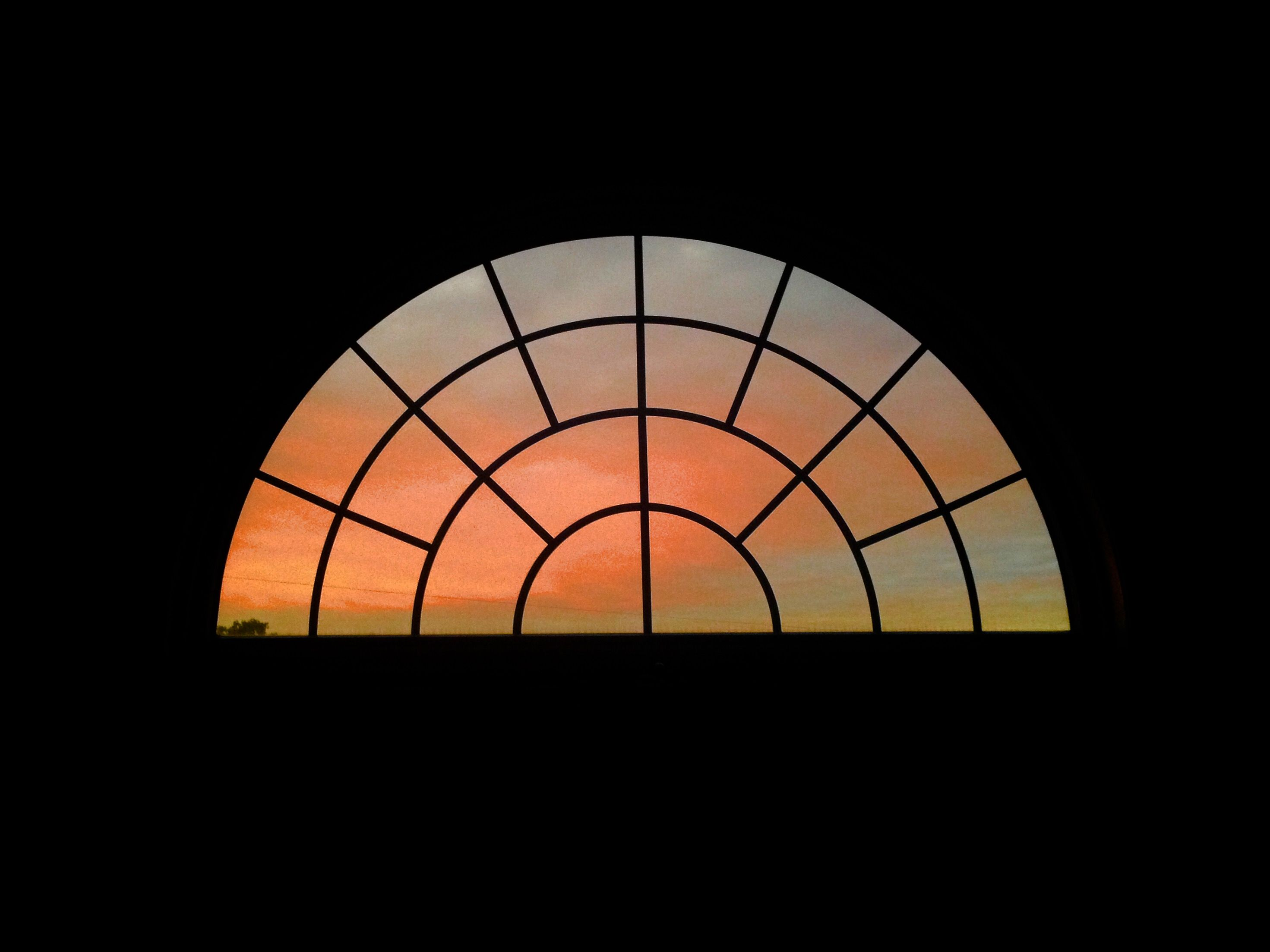 Sunset through the half moon window, in my master bedroom.