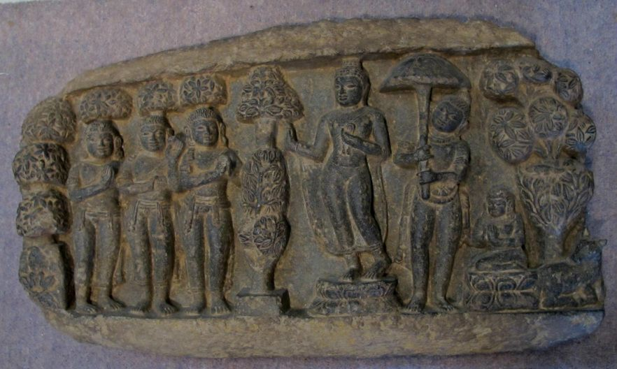 This Gandharan schist panel depicts Buddha's First sermon. After attaining enlightenment, Buddha was rejoined by his ashamed devotees who had previously abandoned him when he became an ascetic. In the Deer Park at Sarnath he thus gave his first teachings. The stylised foliage and the recumbent deer at the far right emphasise the setting.