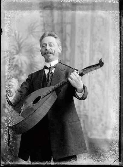 Iloinen tullinhoitaja Ville Poppius äityi soittamaan kuvaamossa mandoliinia 1912.