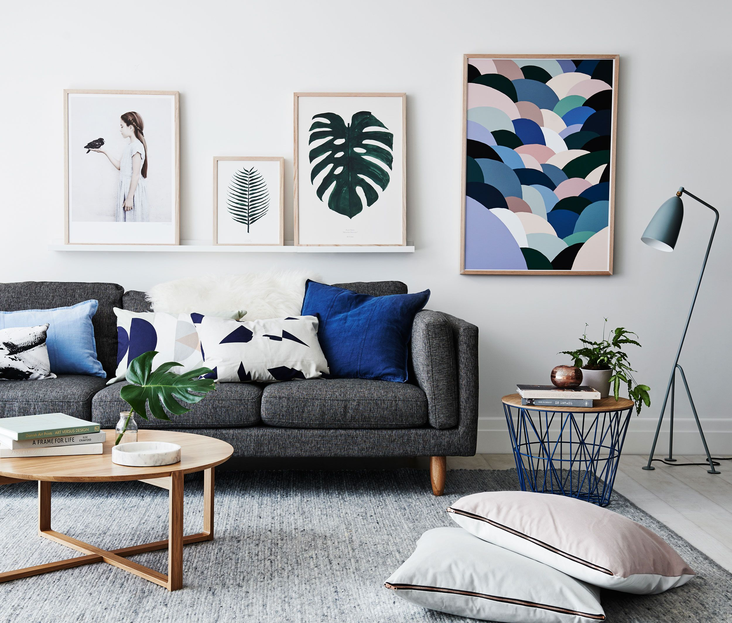 Living room with bold pictures grey sofa and assorted cushions