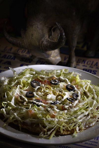 """Ensalada de Colores."" Lettuce salad, fresh tomato, onion, sliced olive & sour cream with salsa on top of crispy tortilla."