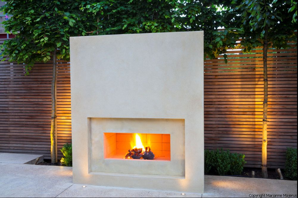 Wood slat wall with uplighting and stone outdoor fireplace ...