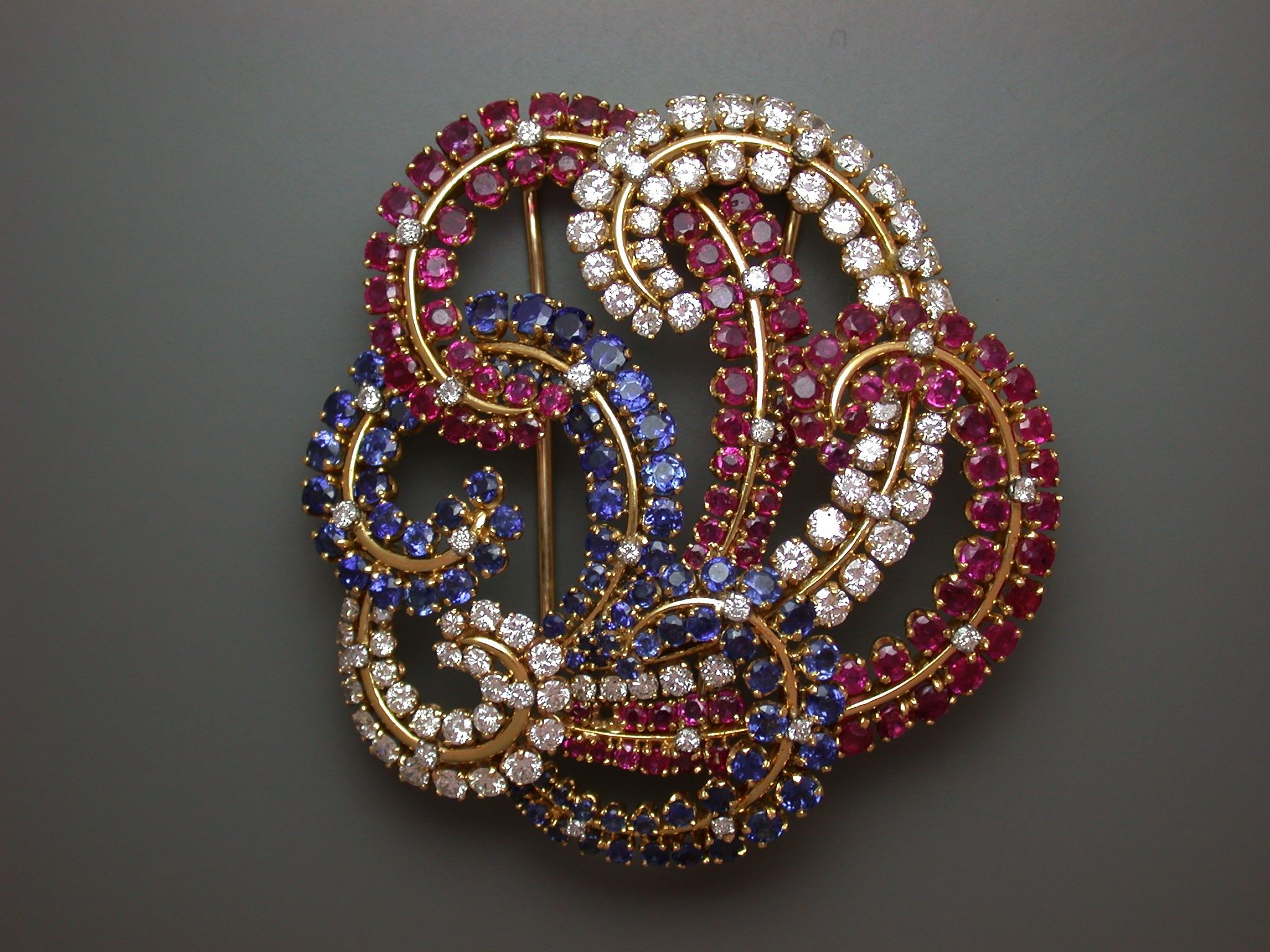 Brooch signed John Rubel, sold by Neil Marrs. In gold diamonds, rubies & sapphires.