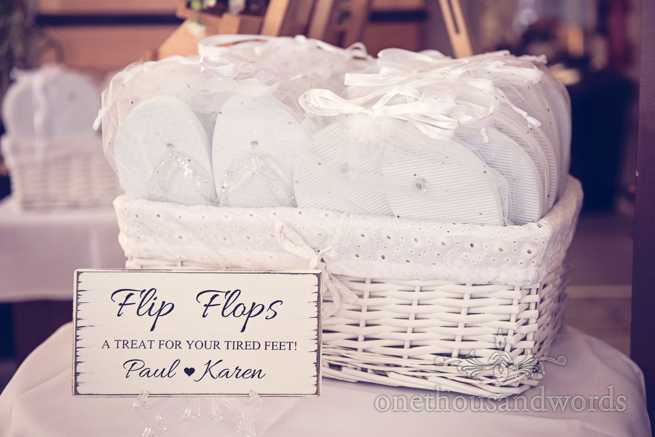 7ada0a7c536 White Wicker basket of white wedding flip flops at Sandbanks Hotel Wedding.  Photography by one thousand words wedding photographers