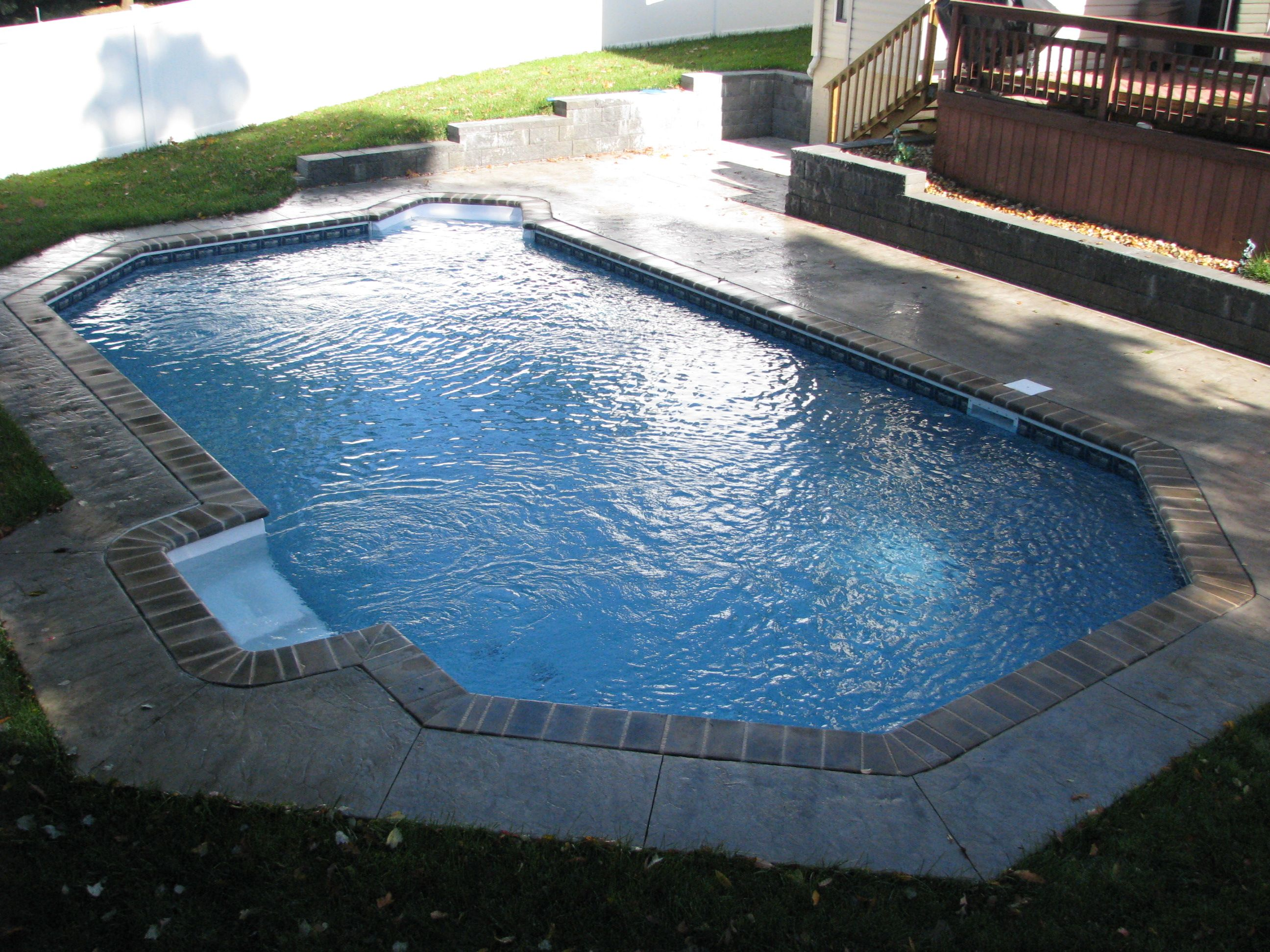 Grecian With Brick Coping Stamped Concrete Patio And Retaining Wall Our Beautiful Swimming