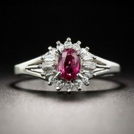 A vibrant bright red, half-carat oval faceted ruby glistens and glows from within a sparkling spray of bright white baguette and round diamonds in this petite but powerful estate ring rendered in gleaming platinum. Measures 3/8 inch. Currently ring size 6 1/2.