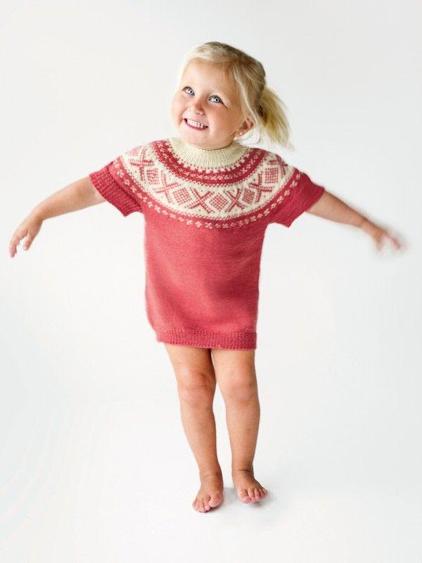 Sjarmerende, kortermet tunika strikket fra toppen og ned, bærestykke med klassisk Cortinamønster. Nivå: Middels. Garnkvalitet: Dale Baby Ull (100 % merinoull, superwash). Fasthet: 32 masker på pinne 2,5 = 10 cm.