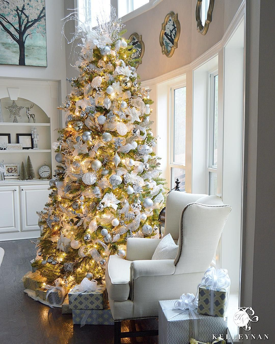 9 foot white gold and silver christmas tree filled with ornaments in two story great room in front of bow of windows check out all the silver and gold