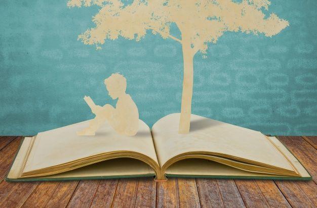 Siluetas de un árbol y un hombre sobre un libro Foto Gratis