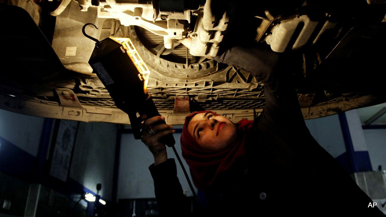 Palestinian auto mechanic Nagham Dweikat checks the bottom of a vehicle at a repair shop