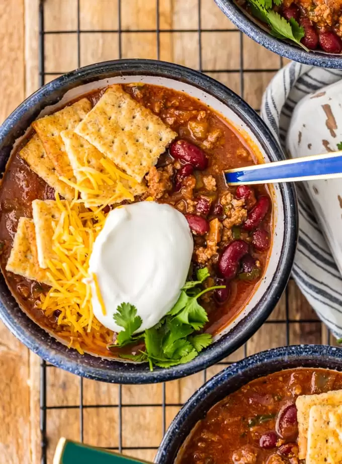 6 Ingredient Chili In A Bowl Topped With Sour Cream And Crackers