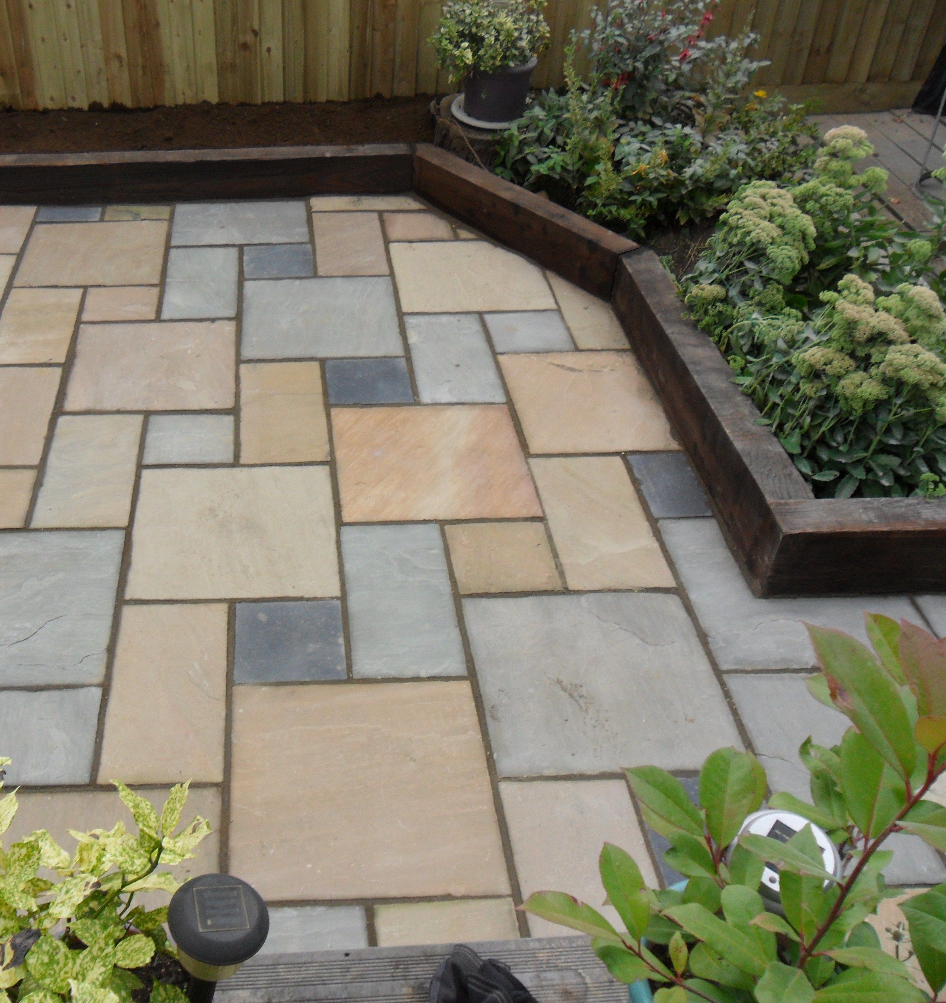 brightly coloured paving with raised flower beds made out of railway sleepers - Garden Design Using Railway Sleepers