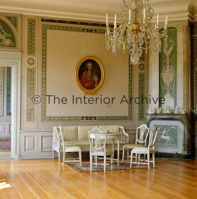 Hylinge In the Salon a Gustavian suite stands beneath a framed portrait and the fireplace is decorated with trompe l'oeil painted panels by Pehr Ljung