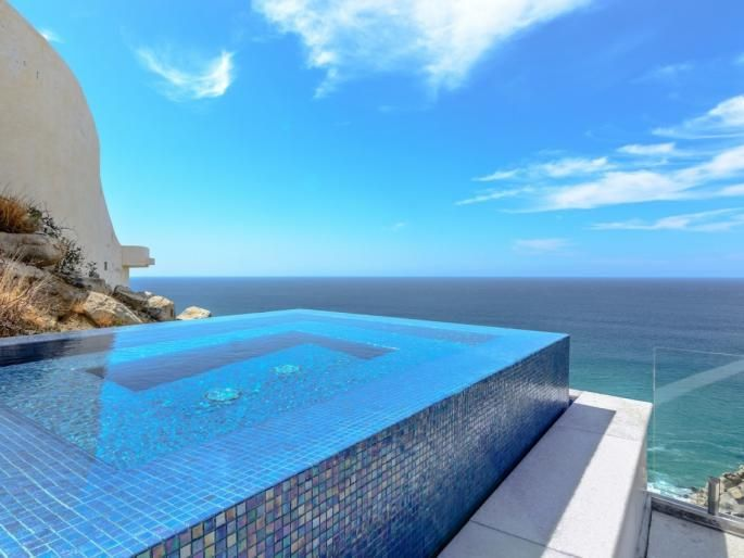 Luxury swimming pool located on a riff with panoramic view on the Pacific Ocean, in Los Cabos, Mexico.
