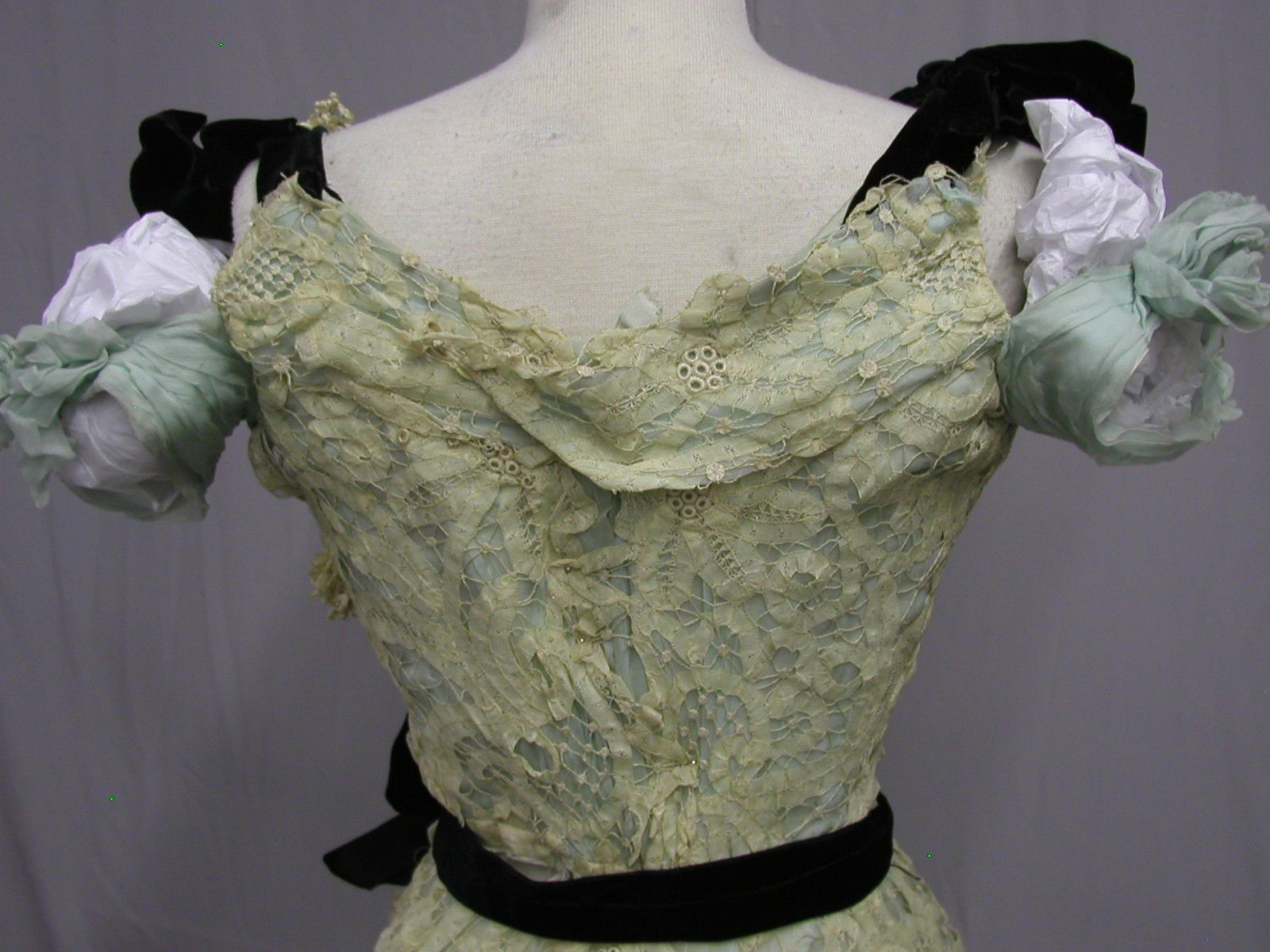 1900 Hand Made Lace & Aqua Silk Ball Gown: It was created at the turn of the 20th century, early 1900. Both shoulders are accented with heavy velvet bows. The hours to make a piece of lace like this by hand are stupendous. Detail