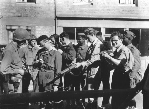 Resistance and soldiers of the US Army review their respective weapons.  In the background, you'll notice several black soldiers—they were riflemen of the French army who had escaped their prison camp that was east of Orne. After their successful escape, they were hidden given shelter in Couterne by the resistance.