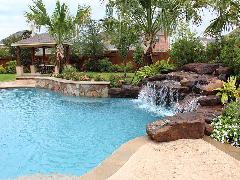 Pin By Pool Pricer On Pool Landscaping And Decking Pool Waterfall Relaxing Backyard Swimming Pool Designs