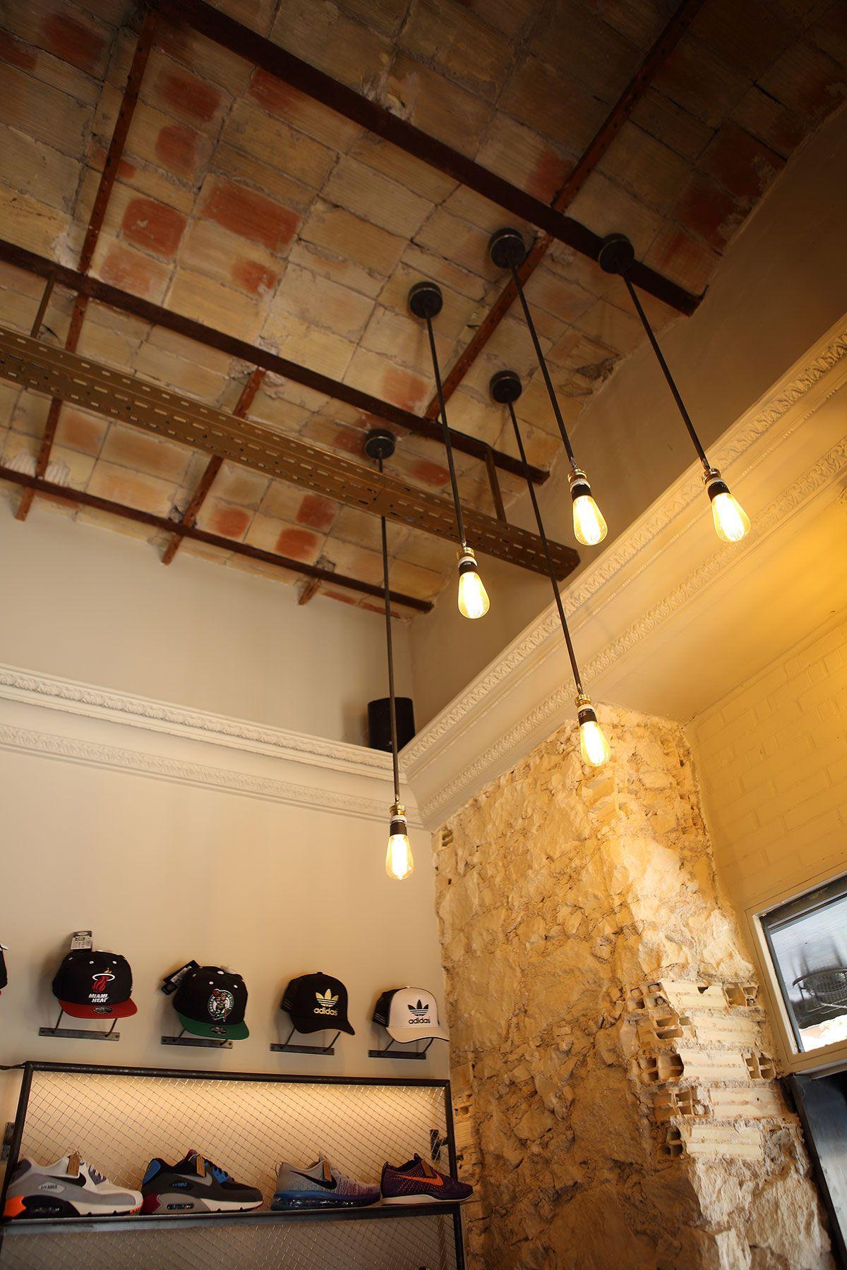 Paredes y vigas de hierro originales a la vista combinadas con lamparas de  diseño propio consiguen un estilo urbano muy propio en esta tienda de  sneakers 20ef82ea7b3