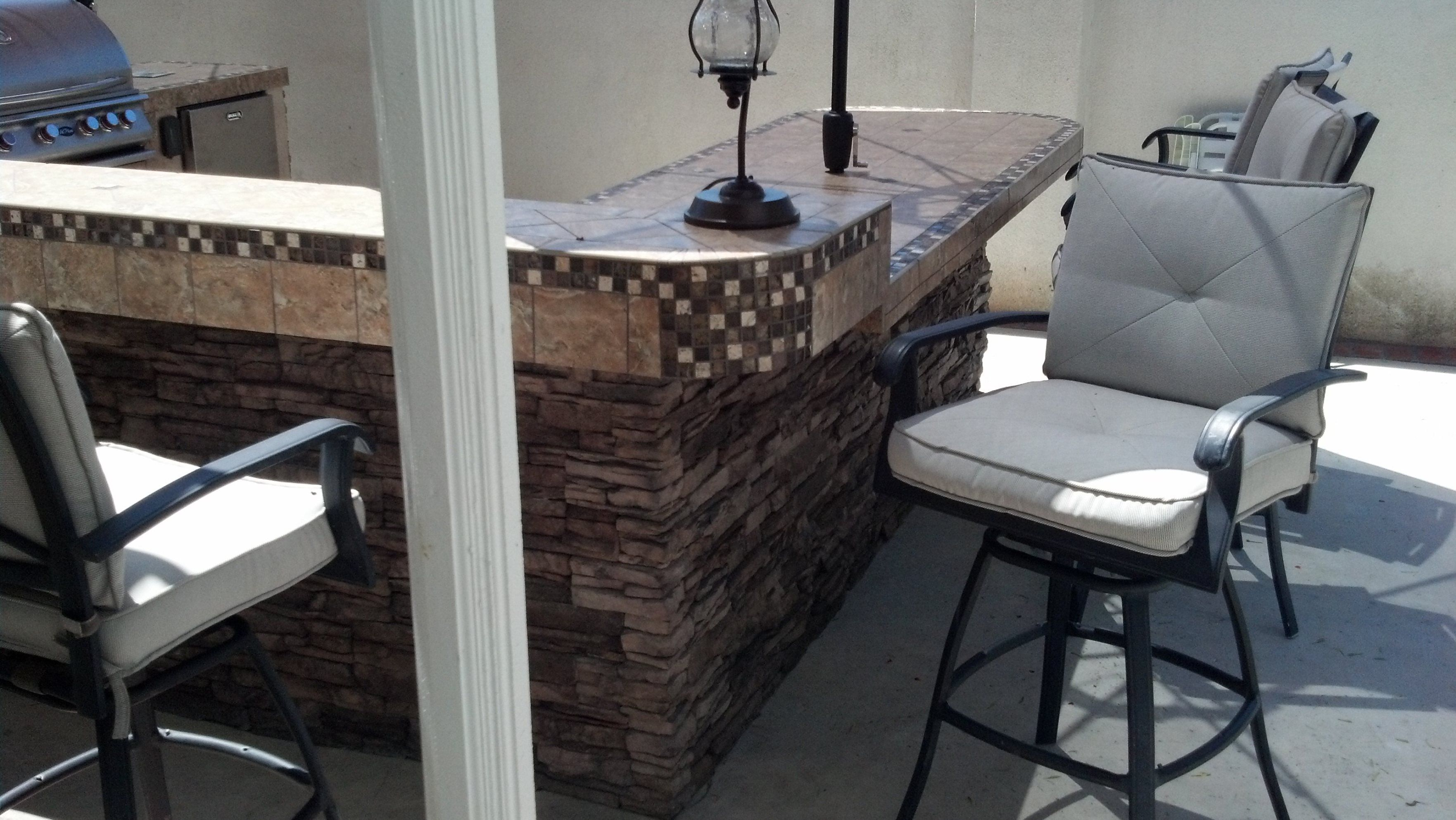 Built-in outdoor kitchen with pizza oven, dual side burner five burner BBQ with confection oven and a searer; two refrigerators; a stand up conversation ledge and sit down eating area, Eldorado stacked stone on the outside on the kitchen