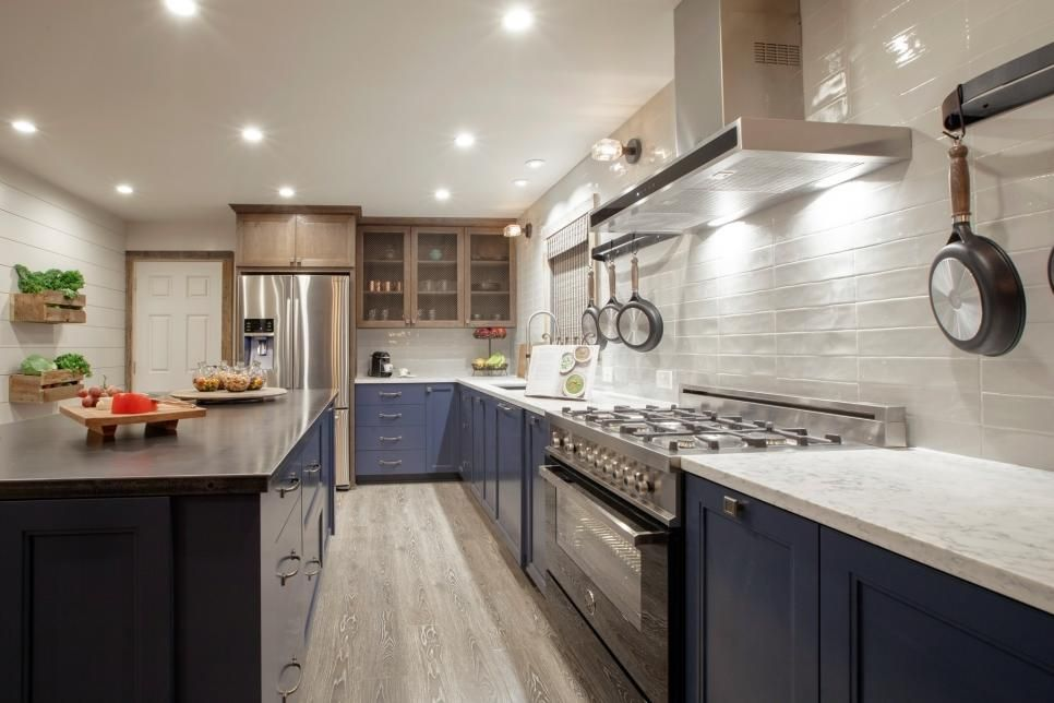 This transitional kitchen features painted blue cabinets paired with oak cabinets and marble ...