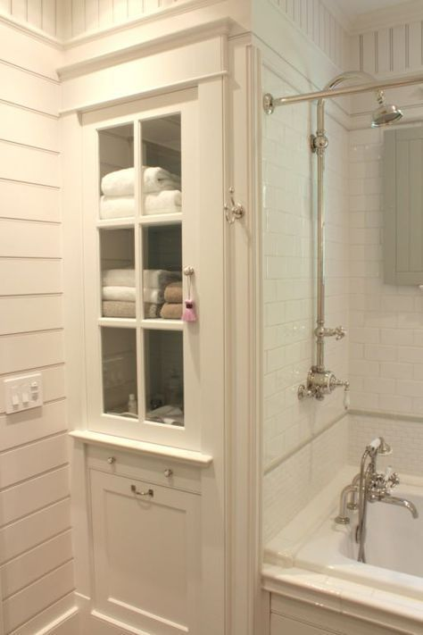 Bathroom linen cabinet and tub surround with white subway tile