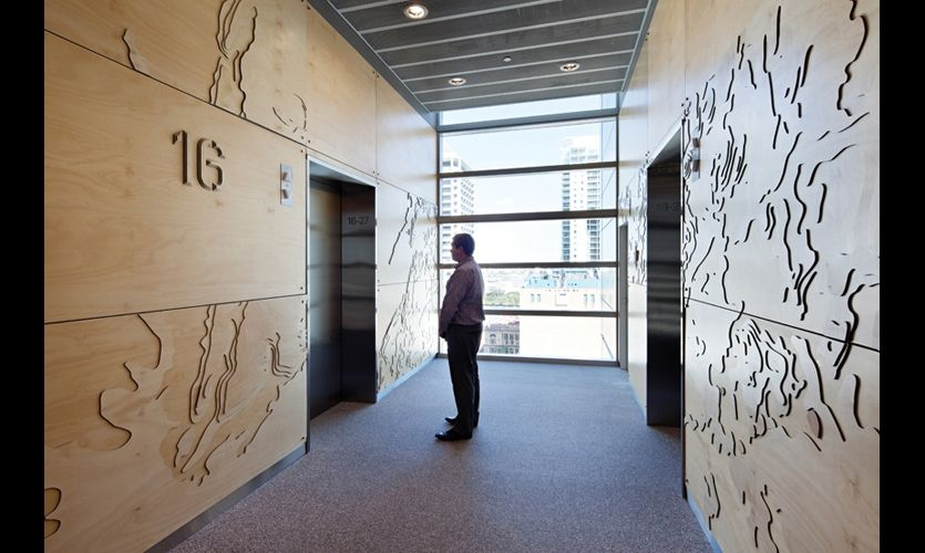 an elevator lobby features a plywood wall relief resembling a