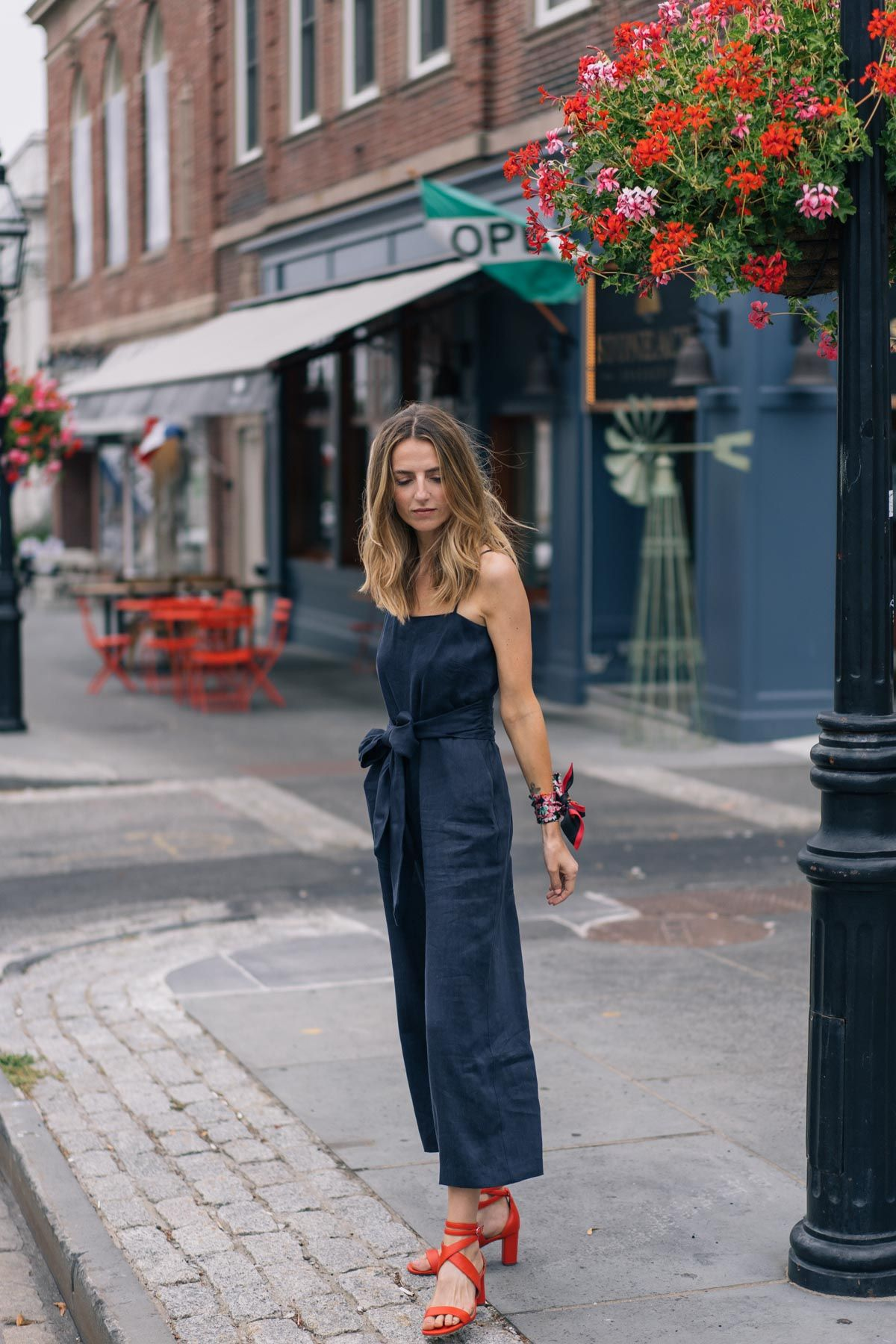 85e14af1edf248 Jess Ann Kirby pairs a navy jumpsuit with bold accessories like red leather  sandals