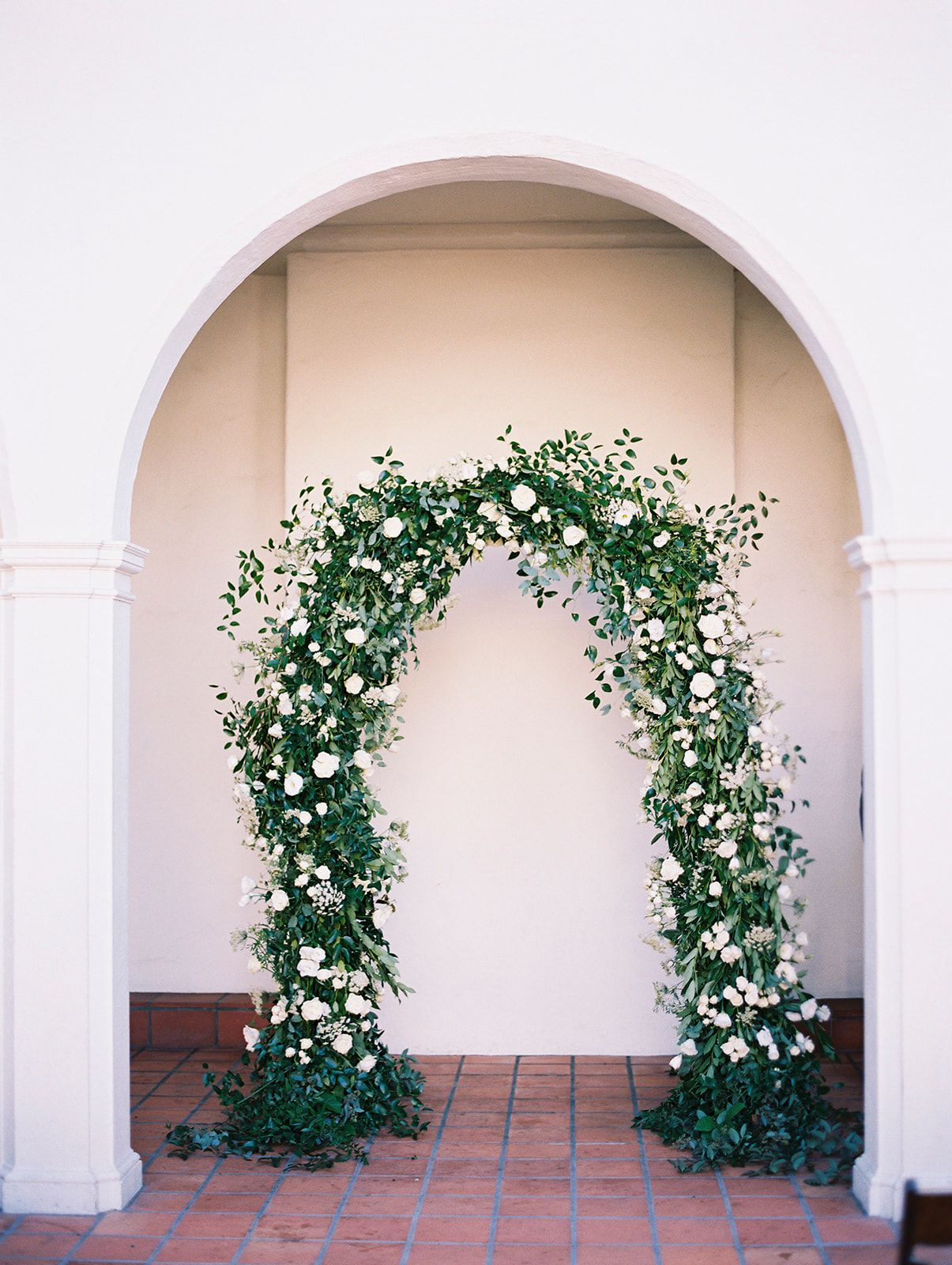White flowers and smilax covered rounded wedding ceremony
