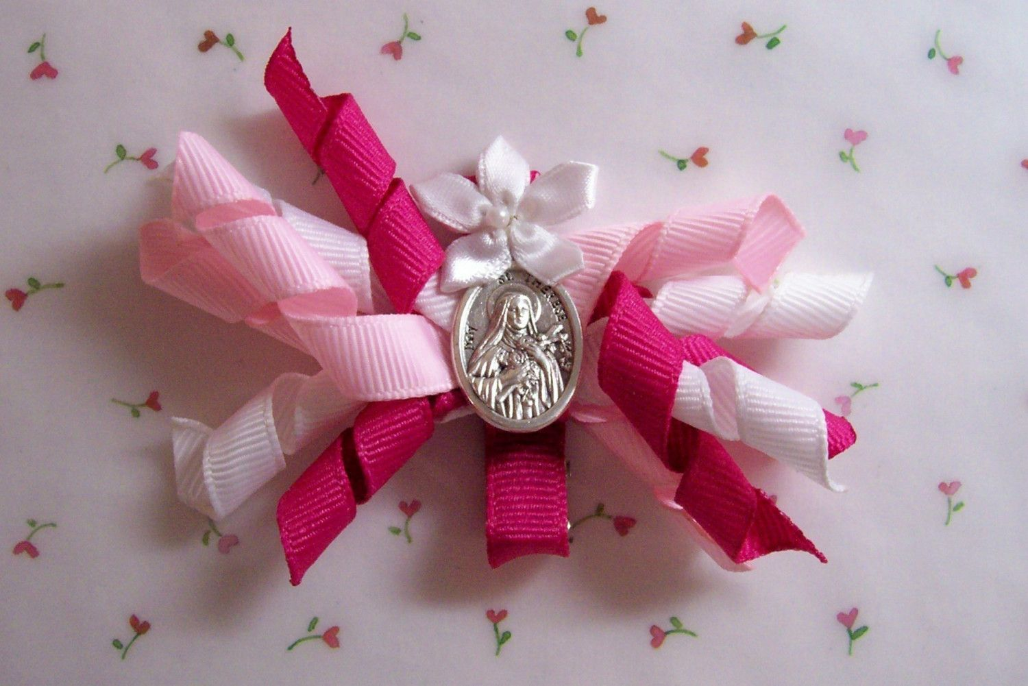 Hair bow with patron saint on it? Would need to do with headband. St. Therese Hair Bow and Holy Card. $7.00, via Etsy.