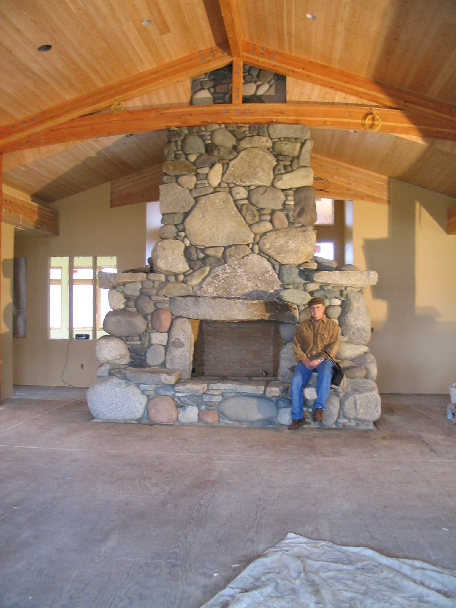 a huge river rock fireplace built by tom and morgan in the house