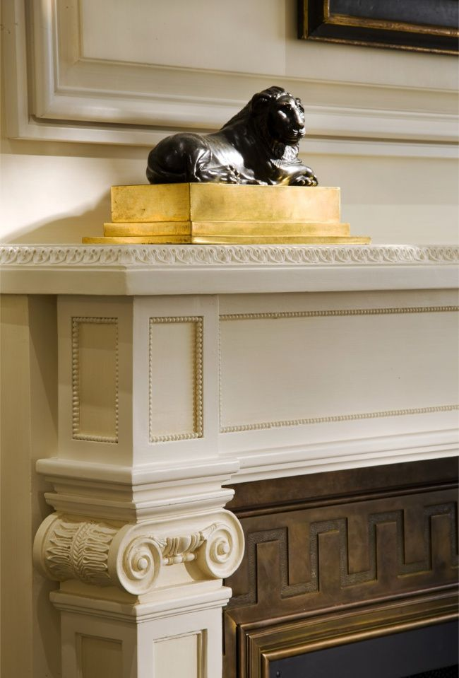 beaded detail inset panels and scrolled columns with bronze inset with greek key on surround