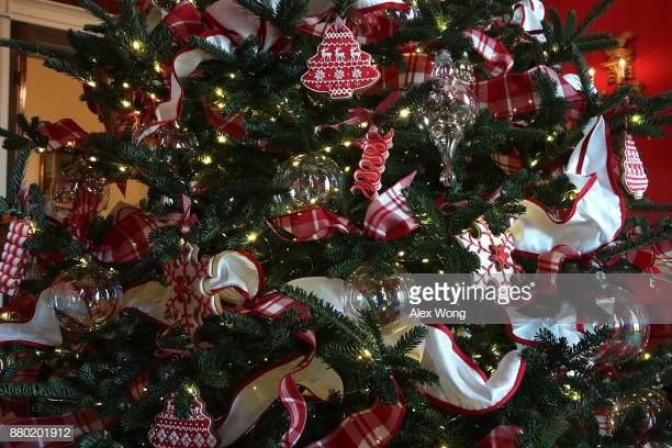 Ornaments are hung on a Christmas tree in the Red Room at the White