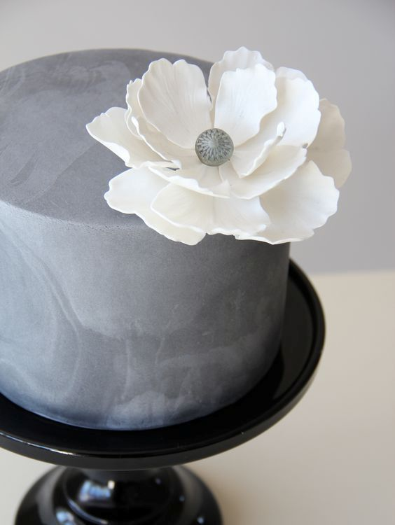 Textural concrete wedding cake with a large white flower food a textural concrete wedding cake with a large white flower mightylinksfo