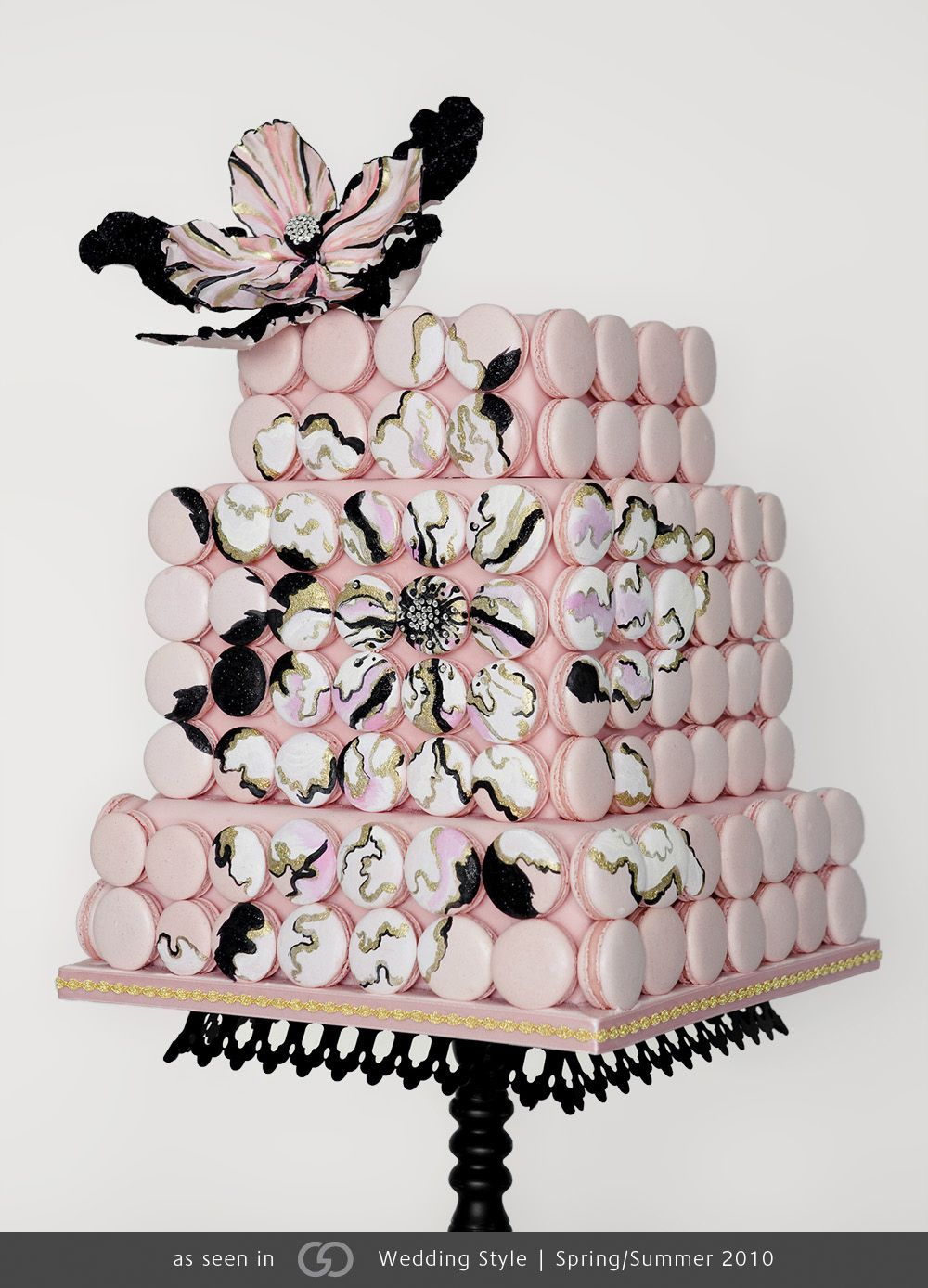 Square cake encrusted with hand-painted macaroons featuring sugar flower topper.