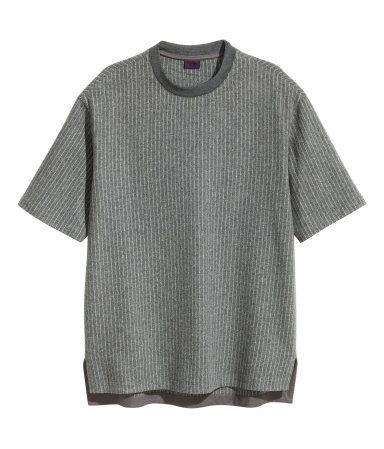 Grijs/gestreept. Een T-shirt van wolmix met een dessin met smalle strepen. Het model heeft een geribde bies rond de halsopening, een iets langer achterpand