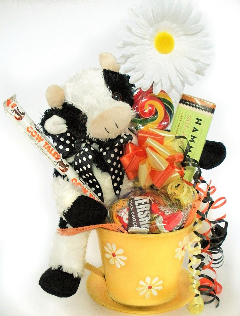"This ""moo""licious Cow Candy Gift Bouquet is udderly irresistible!  It features our Bossy the Cow ""Lean Bean"" Bearington Plush, from the award winning Bearington Bear Collection.  Plus our big Tin Teacup and Saucer with Daisies All Over, filled w/ lots of popular chocolates, and topped with a ""Hammond's"" Hand-Pulled Lollipop, and a ""Hammond's"" Gourmet Chocolate Bar.  Embellished w/ our frilly Silk White Daisy, a Handmade Bow w/ lots of Curly Ribbons, and of course, a Cow Tales Candy Stick!"
