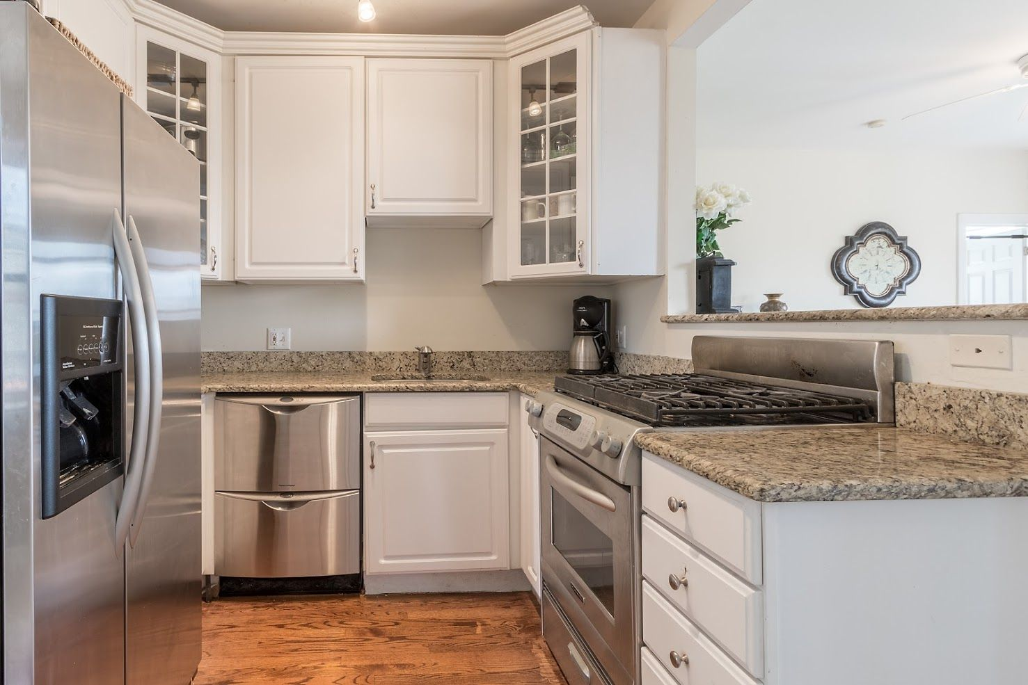 Modern Kitchen With White Cabinets Glass Doors Hardwood Floors Granite Countertops Stainless Steel Appliances Kitchen Remodel Updated Kitchen Maple Floors