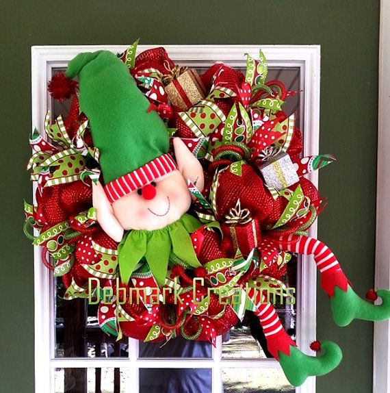 This playful elf will delight you guests of all ages for many Christmas seasons to come.  Wreath is made with poufs of red premium deco mesh.  It is adorned with four styles of designer Christmas ribbon streamers along with red and green flex tubing bows.  An adorable elf is kicking up his heels as he prepares gifts for all the children. Three glittery gifts are scattered about the wreath.  All ribbons are wired and can be rearranged as desired.  Wreath measures approximately 25 and 7 deep…